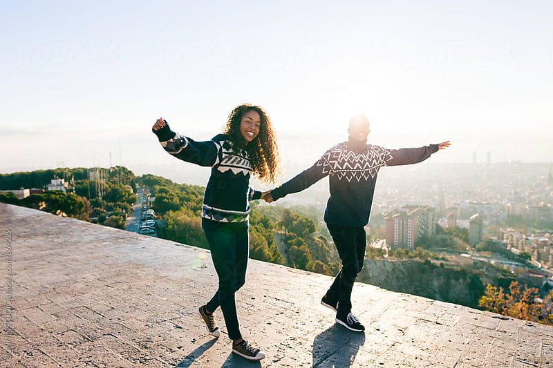 Young couple having fun holding hands above Barcelona. by BONNINSTUDIO for Stocksy United