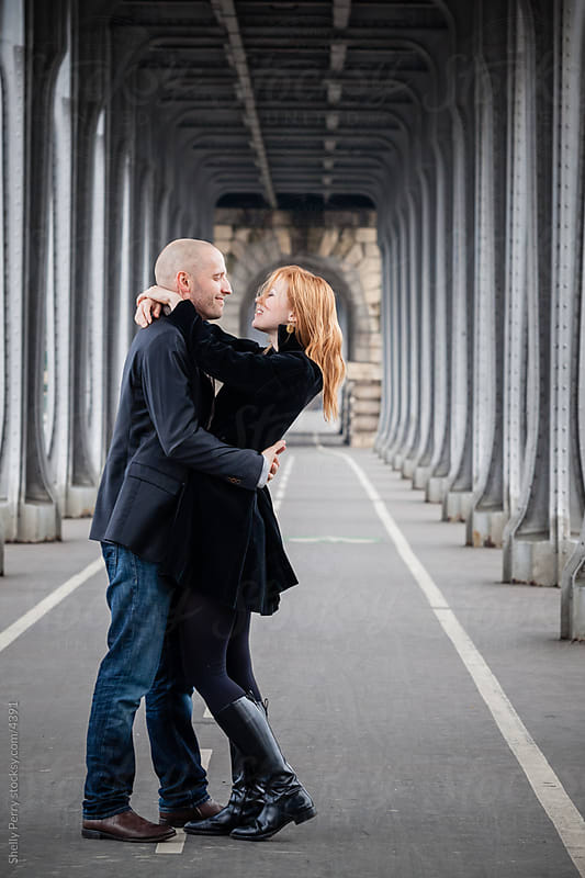 Romantic couple embrace under a bridge in Paris by Shelly Perry for Stocksy United