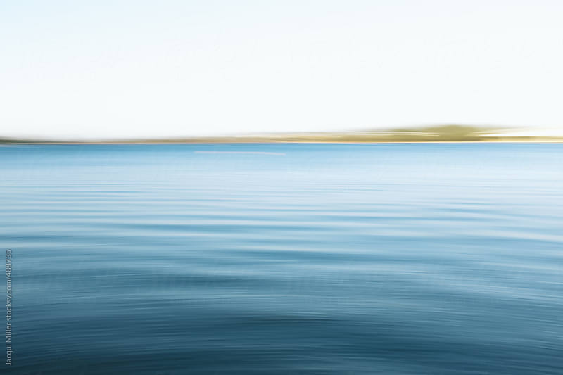 Motion blur of a river with land on the horizon by Jacqui Miller for Stocksy United