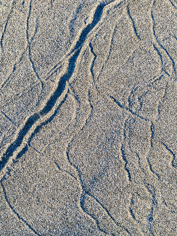 Close up of markings on beach sand by Paul Edmondson for Stocksy United