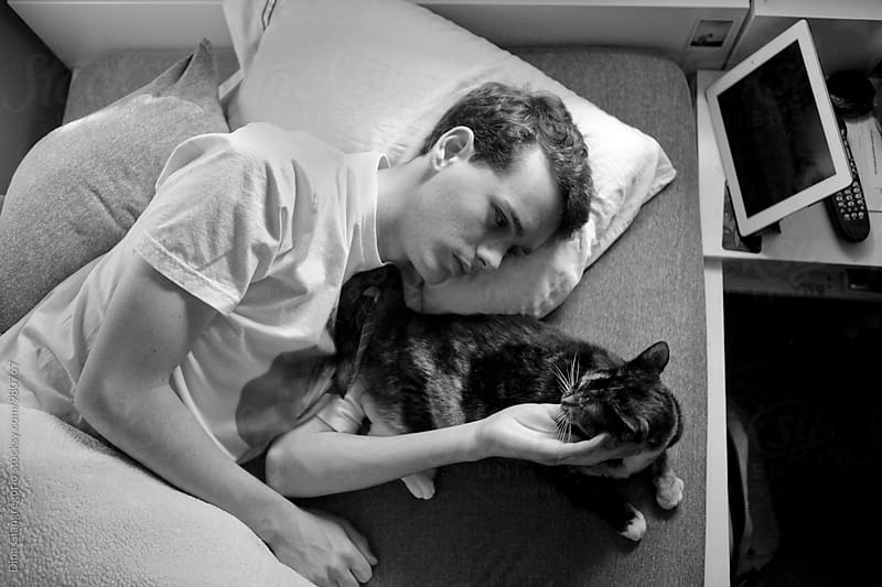 Teenage Boy In Bed  Petting Cat With Tablet Nearby by Dina Giangregorio for Stocksy United