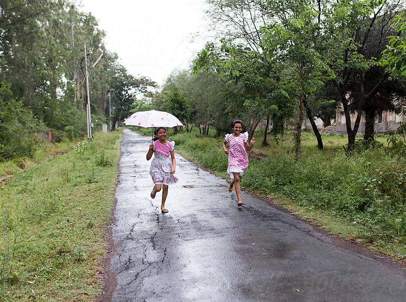 Teenagers running throgh a road in monsoon season by PARTHA PAL for Stocksy United