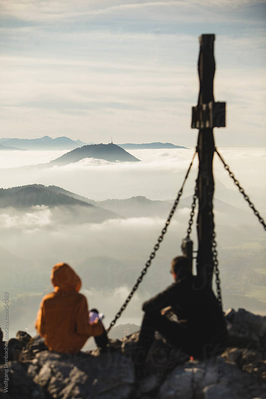 two people sitting next to a summit cross on a mountain watching the mist below by Wolfgang Lienbacher for Stocksy United