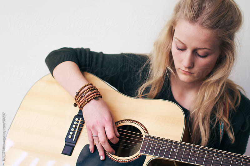 Teenage girl playing a guitar by Jacqui Miller for Stocksy United