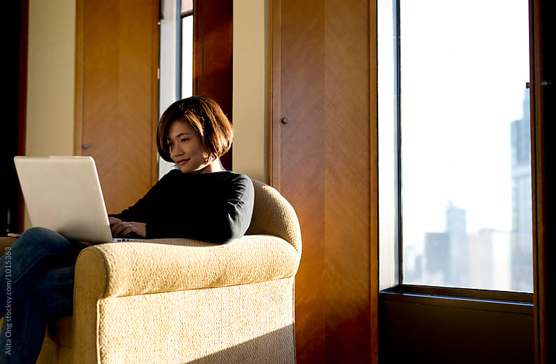 Woman sitting on a sofa using a laptop by Alita Ong for Stocksy United