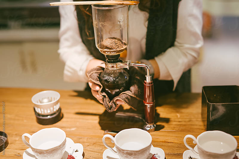 Female coffee shop owner preparing coffee at counter by MaaHoo Studio for Stocksy United