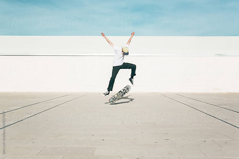 Young man performing a skate trick by Vera Lair for Stocksy United