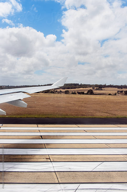 Airplane touches down at the landing  strip of an Australian airport viewed from inside the plane by Angela Lumsden for Stocksy United