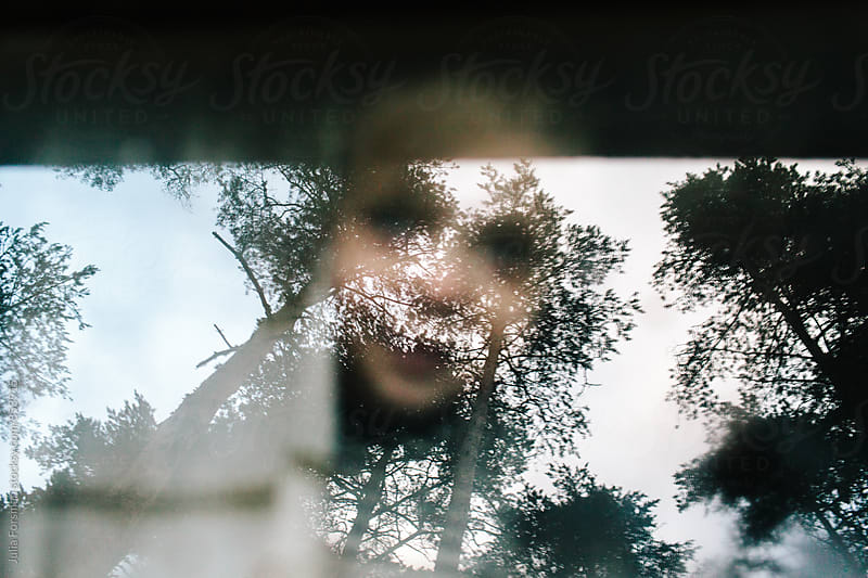 Surreal image of a child through a window with trees reflected on it. by Julia Forsman for Stocksy United