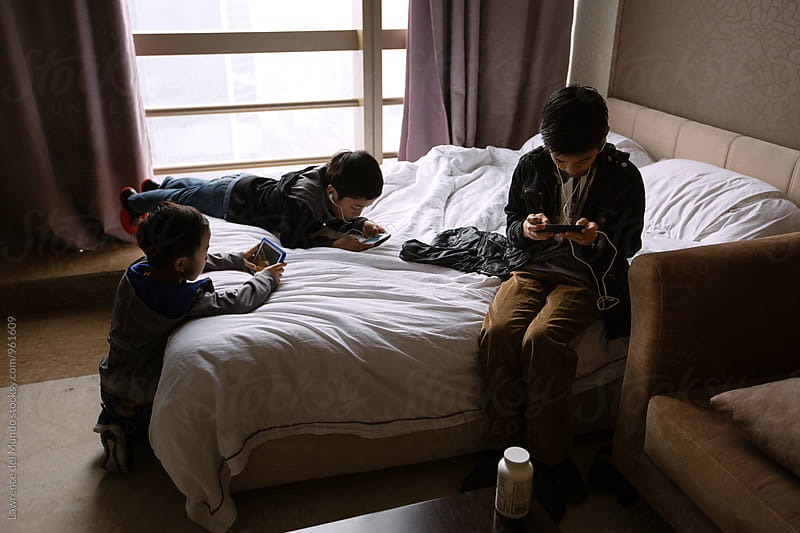 Three young boys busy with their gadgets in a hotel room by Lawrence del Mundo for Stocksy United
