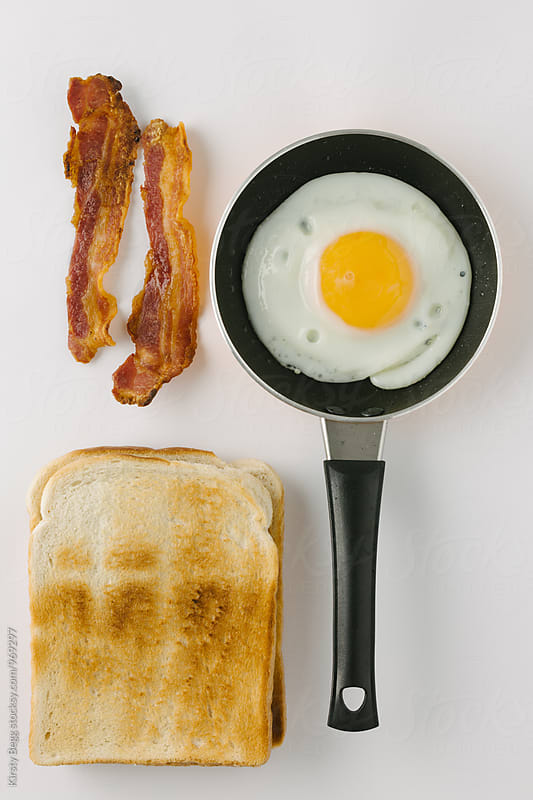 Frying pan with a fried egg with toast and bacon, flat lay breakfast by Kirsty Begg for Stocksy United