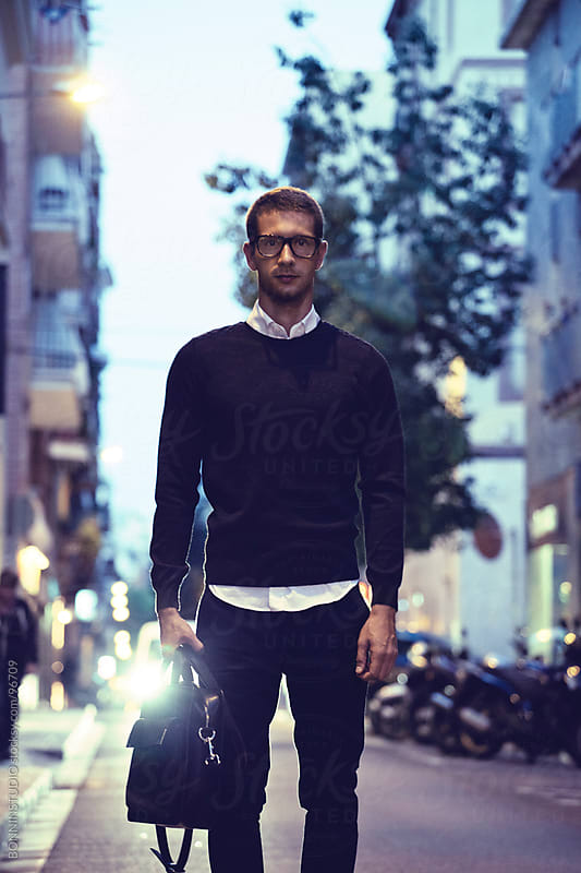 Modern businessman holding black briefcase in the street. Night scene. by BONNINSTUDIO for Stocksy United