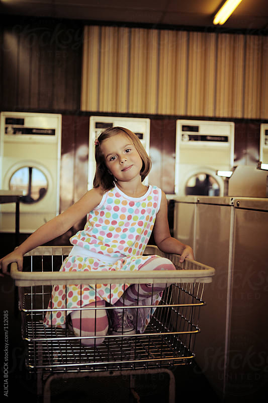 Girl At The Laundry Mat - Vertical by ALICIA BOCK for Stocksy United