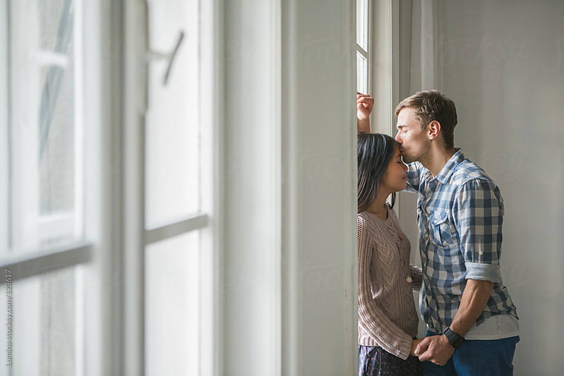 Couple Standing by the Window by Lumina for Stocksy United