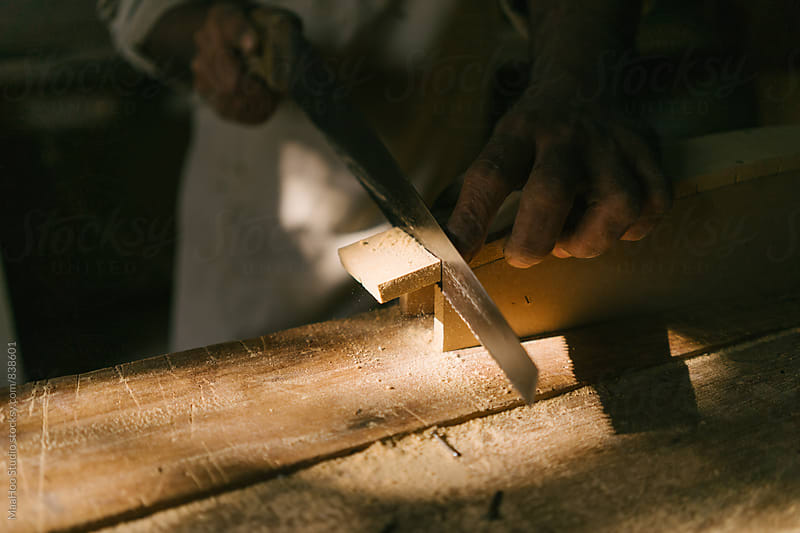 Carpenter sawing wood by MaaHoo Studio for Stocksy United