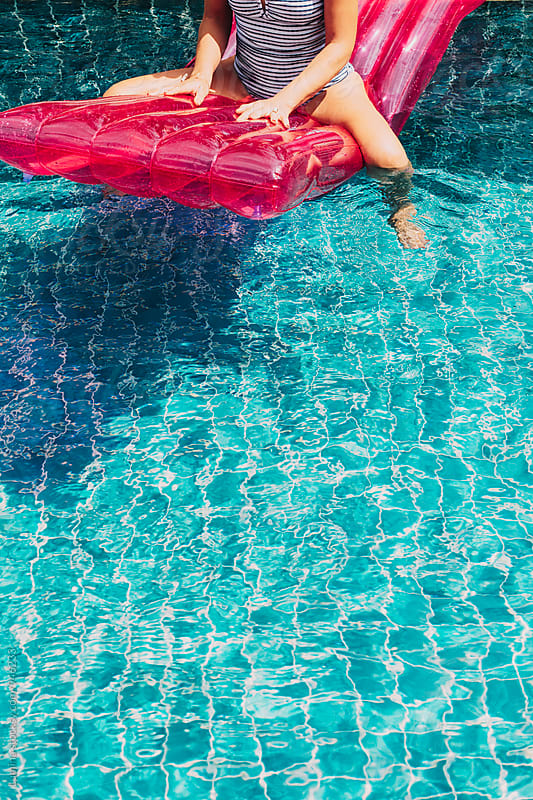 Woman Sitting on a Sea Mattress in a Swimming Pool by Lumina for Stocksy United