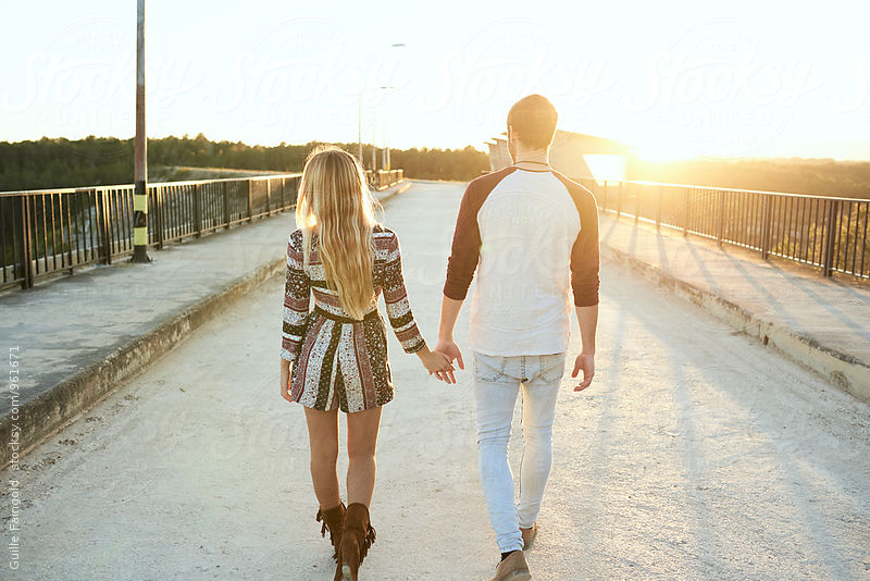 Back view of young couple walking at sunset by Guille Faingold for Stocksy United