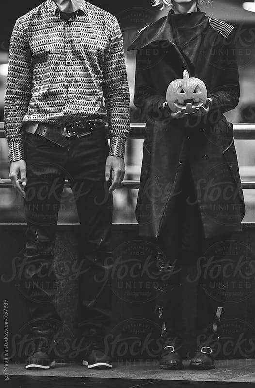masked couple with a Halloween pumpkin,black and white by Igor Madjinca for Stocksy United