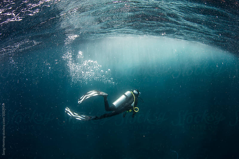 Scuba diver under wave by Song Heming for Stocksy United
