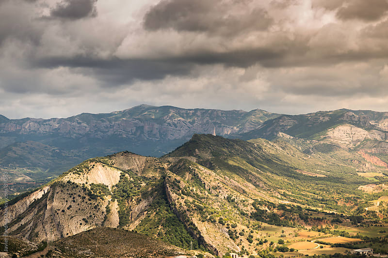 Landscape of valley with cloudy sky by Javier Pardina for Stocksy United
