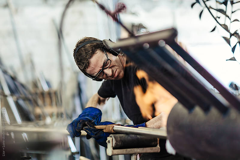Man placing steel poles in forge by Lior + Lone for Stocksy United