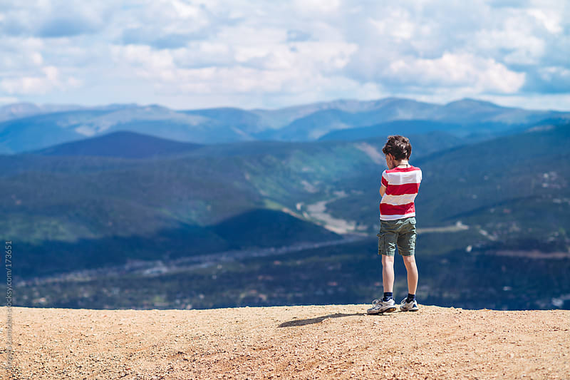 Boy standing high above a mountain town  by Angela Lumsden for Stocksy United