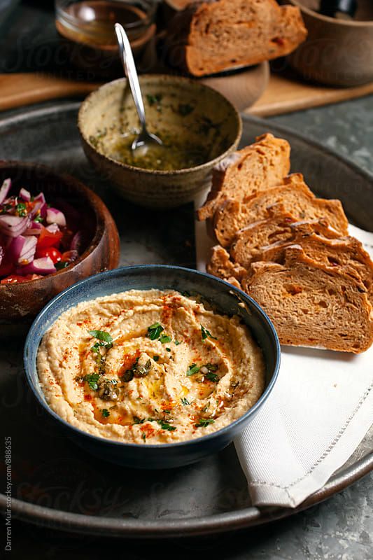 Hummus breads and salads on a serving tray. by Darren Muir for Stocksy United