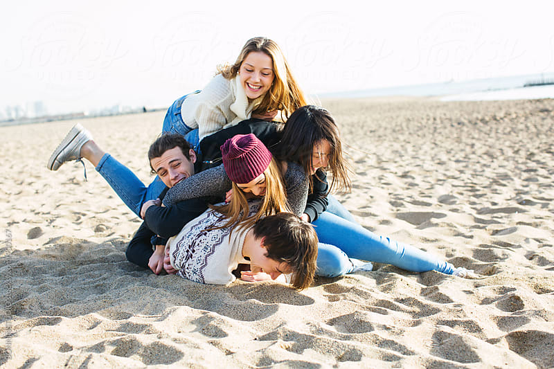 Group of teenage friends having fun on the beach. by BONNINSTUDIO for Stocksy United
