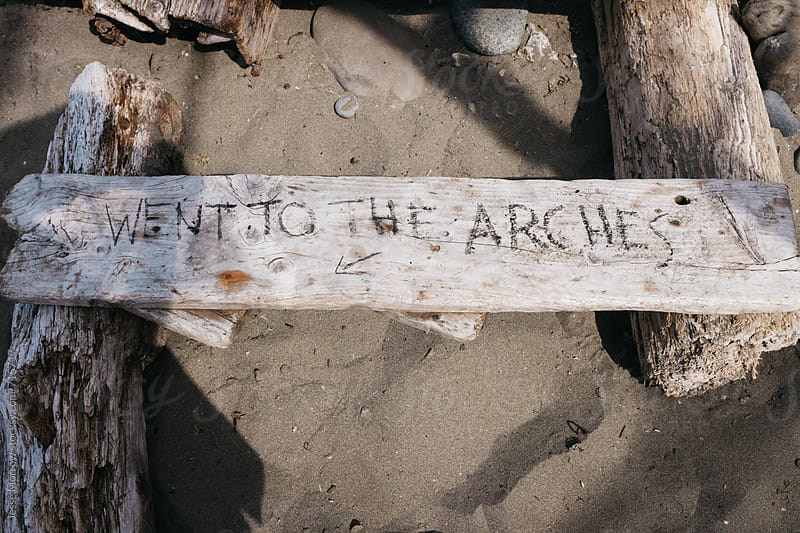 hand written note on driftwood at beach while camping by Jesse Morrow for Stocksy United