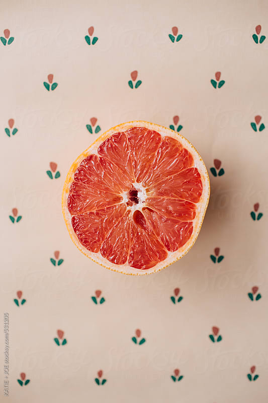 Grapefruit half sitting on a patterned table by KATIE + JOE for Stocksy United