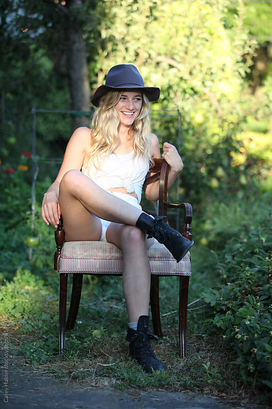 A Beautiful Young Woman Smiling While Sitting In A Garden by Carey Haider for Stocksy United