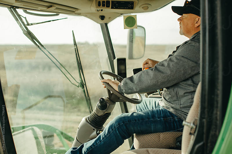 Man driving combine while farming. by Luke Liable for Stocksy United