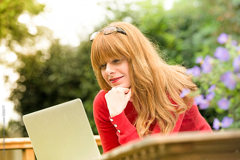 Woman working from home in her garden by Craig Holmes for Stocksy United