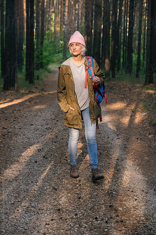 Smiling young backpacker in pink hat walking in forest by Danil Nevsky for Stocksy United