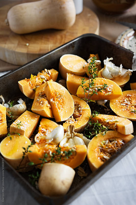 Butternut squash,smoked garlic and thyme in a roasting tin,ready to be cooked. by Darren Muir for Stocksy United