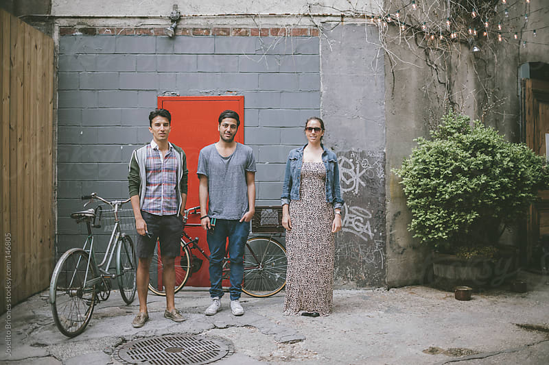 Casual Friends Standing by Bicycles in a City Courtyard by Joselito Briones for Stocksy United