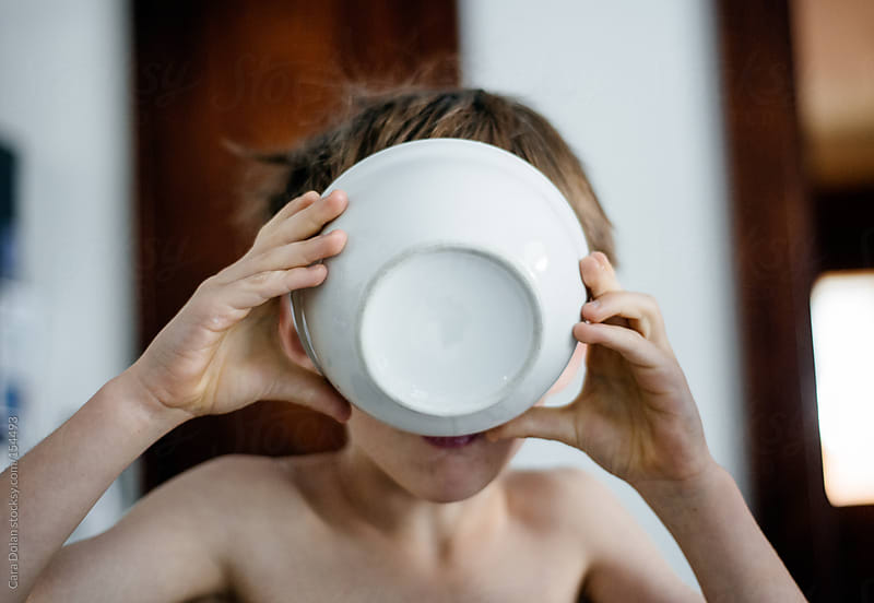 Boy drinks the milk from his cereal bowl by Cara Dolan for Stocksy United