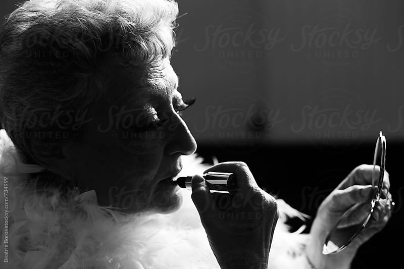 Senior theatrical woman puts on lipstick by Beatrix Boros for Stocksy United