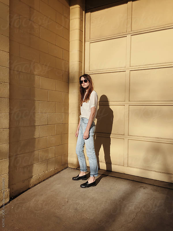 Woman standing near a yellow building in the sun by KATIE + JOE for Stocksy United