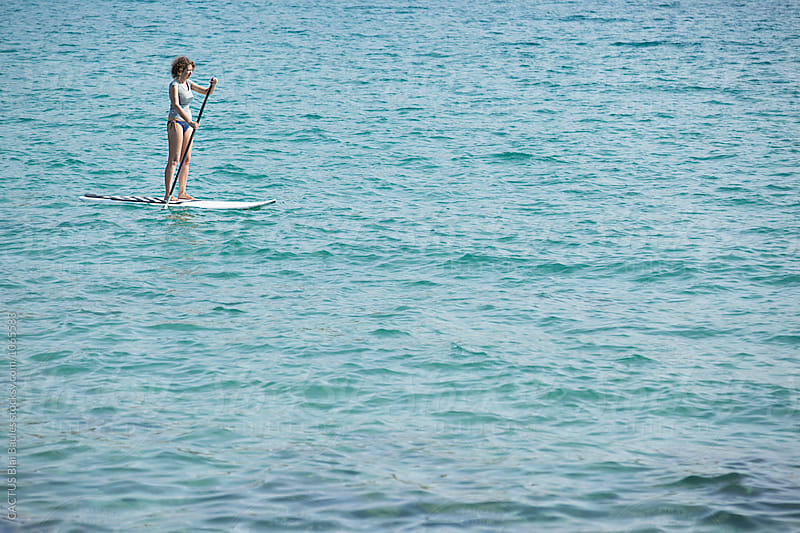 Woman doing Stand Up paddle Surf by CACTUS Blai Baules for Stocksy United