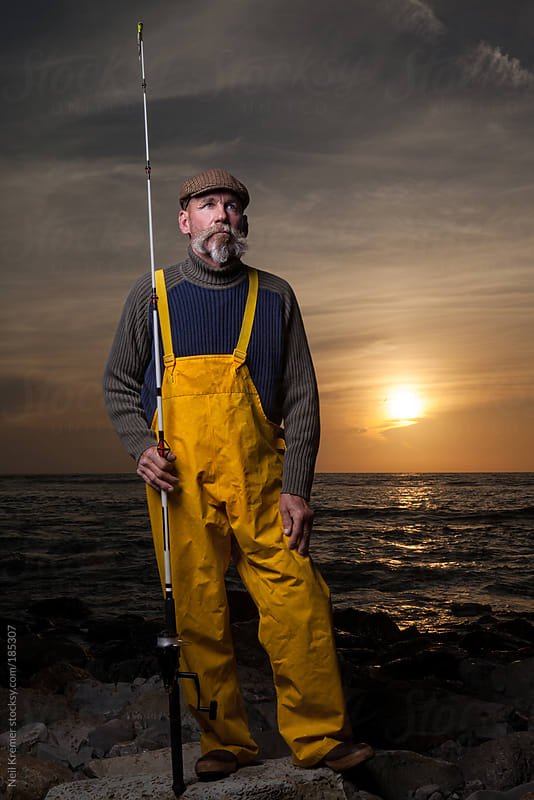 Fisherman standing by the sea at dusk by Neil Kremer for Stocksy United