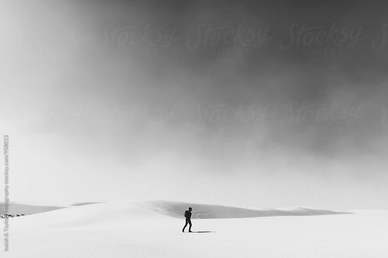 Person walking through sandy desert by Isaiah & Taylor Photography for Stocksy United
