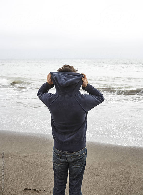 Young man in hoodie on the beach in California  by Trinette Reed for Stocksy United