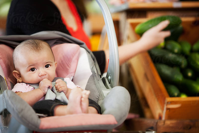 Market: Cute Baby in Carrier with Mother in Background by Sean Locke for Stocksy United