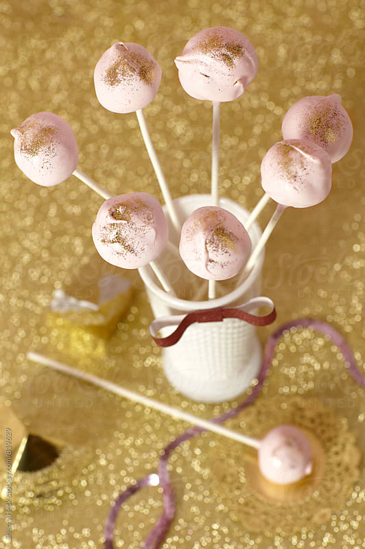 Pink meringues on sticks at party on gold glitter background by Sherry Heck for Stocksy United