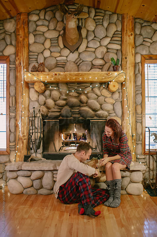 Cozy couple in pajamas sitting by fireplace by Kristin Rogers Photography for Stocksy United