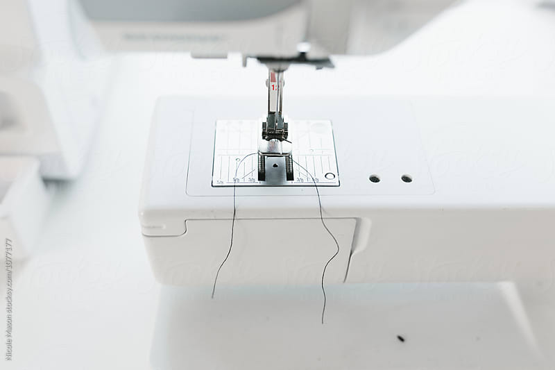 close up of sewing machine in bright white studio by Nicole Mason for Stocksy United