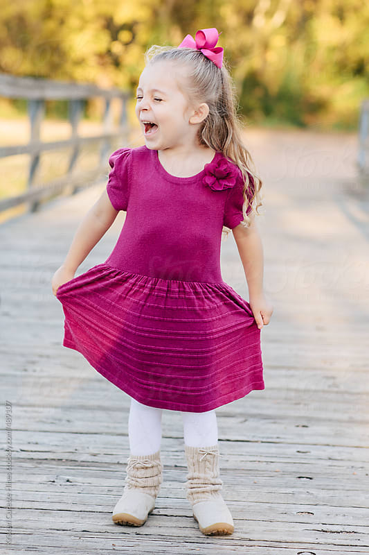 An excited little girl in a pink dress by Kristen Curette Hines for Stocksy United