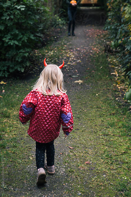 Little girl wearing red horns for Halloween by Lior + Lone for Stocksy United