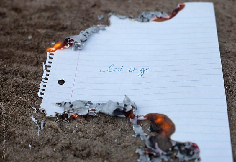 Burning a handwritten message saying Let it Go by Carolyn Lagattuta for Stocksy United